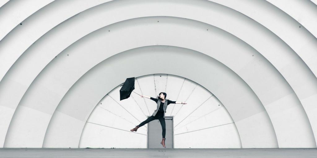 kobieta w czerni skacze z parasolem na tle struktury architektonicznej