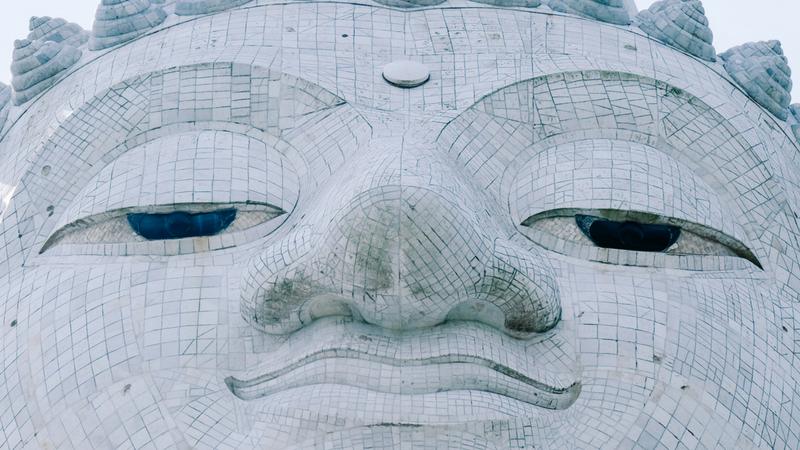 zbliżenie na twarz przedstawiającej patrzącego z góry Buddę statuy
