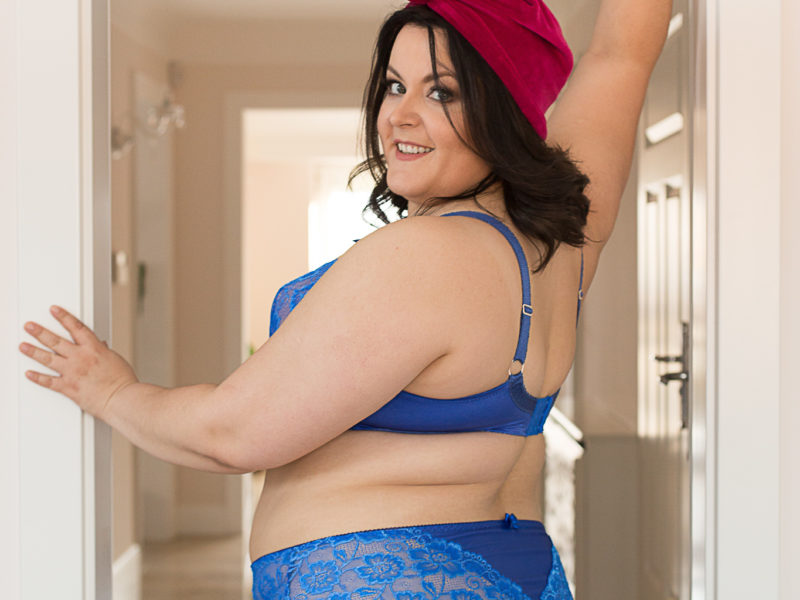 Ula ubrana wa niebieski komplet bielizny stoi w drzwiach i ogląda się przez ramię. Na głowie ma czerwony turban.
