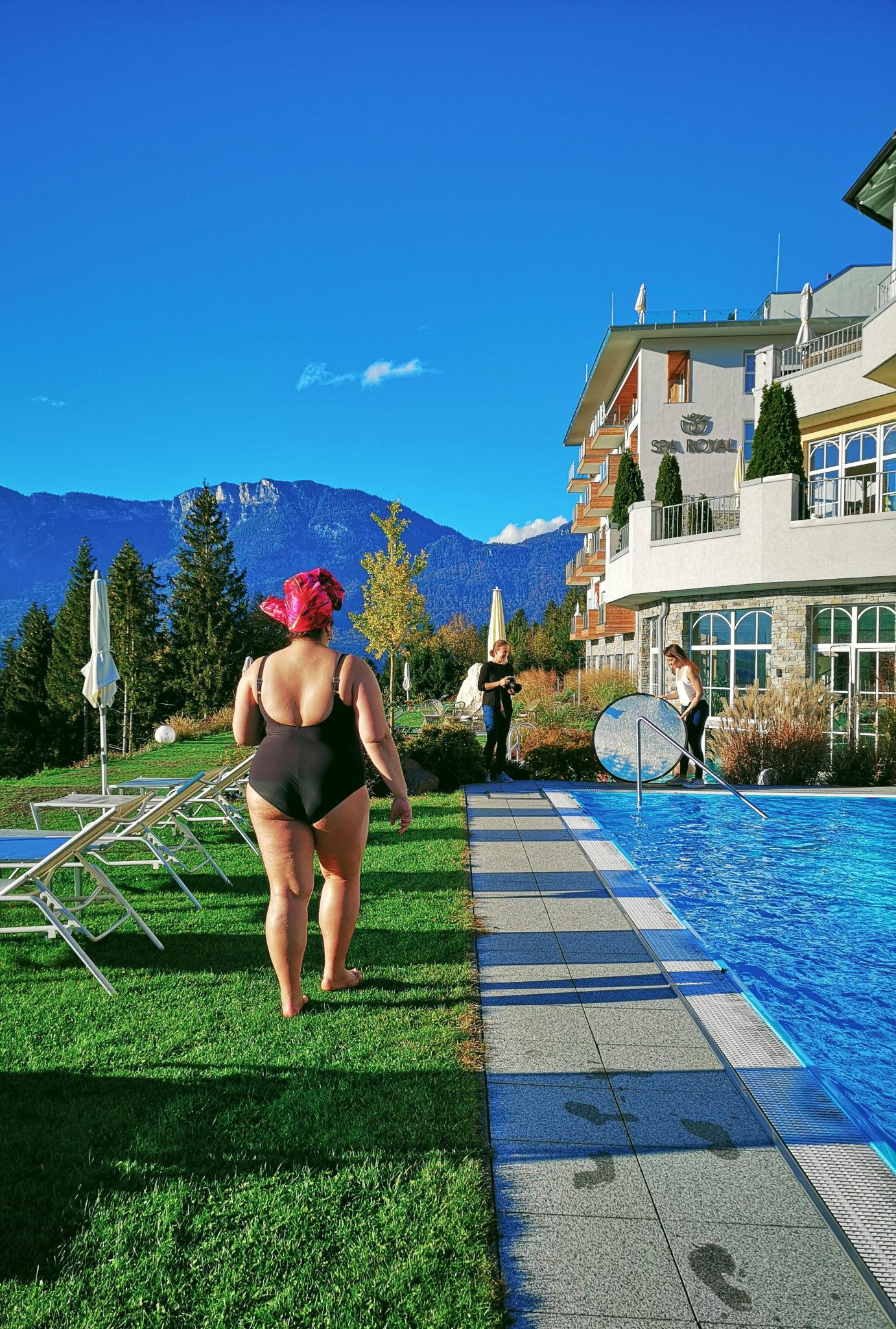 Widok na kawałek basenu i hotelu, Ula w kositumie kąpielowym i turbanie widzie w kierunku fotografki