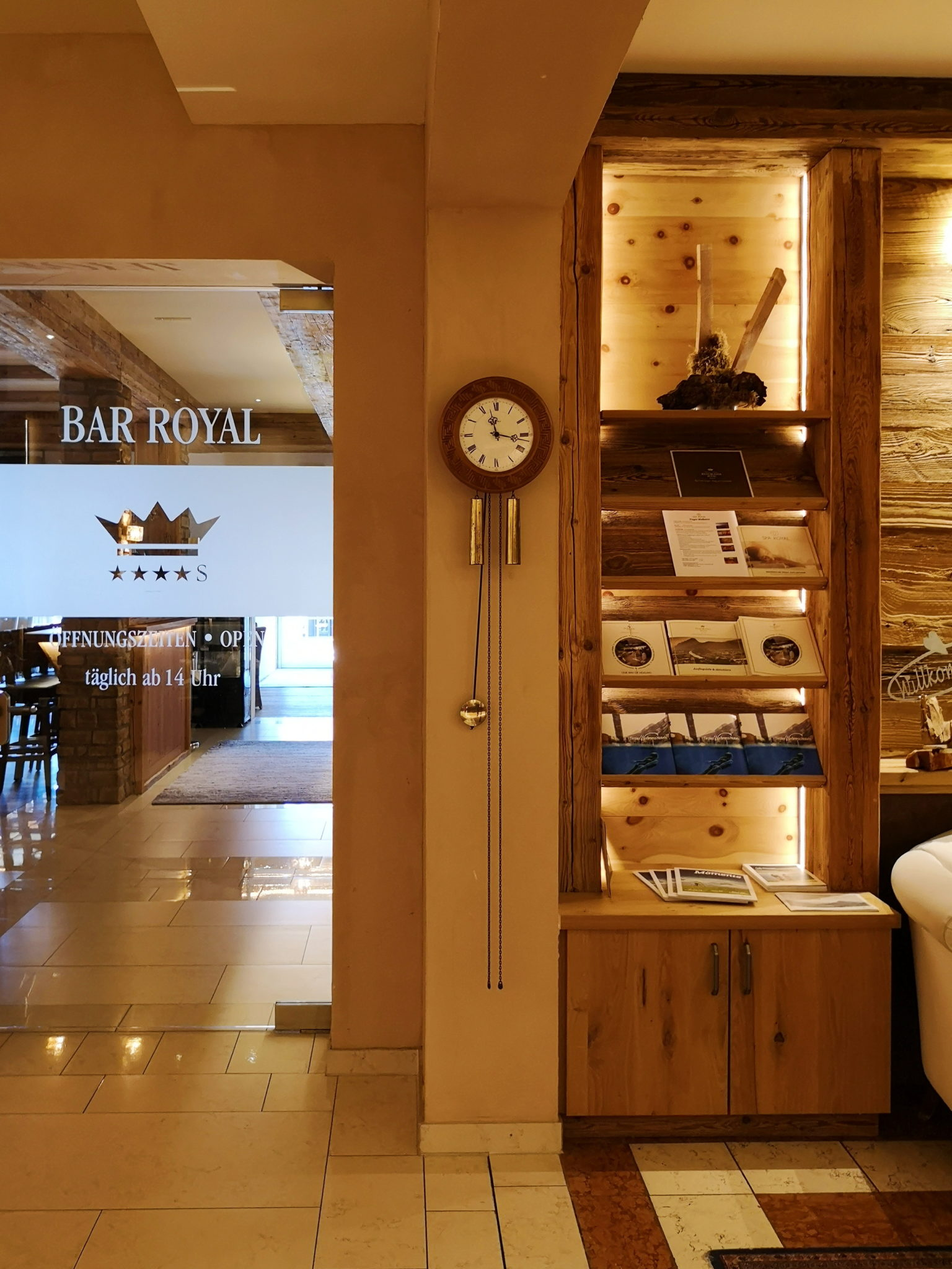 lobby hotelowe z widokiem na wejście do baru, zegar z wahadłem i drewniany, podświetlony regał