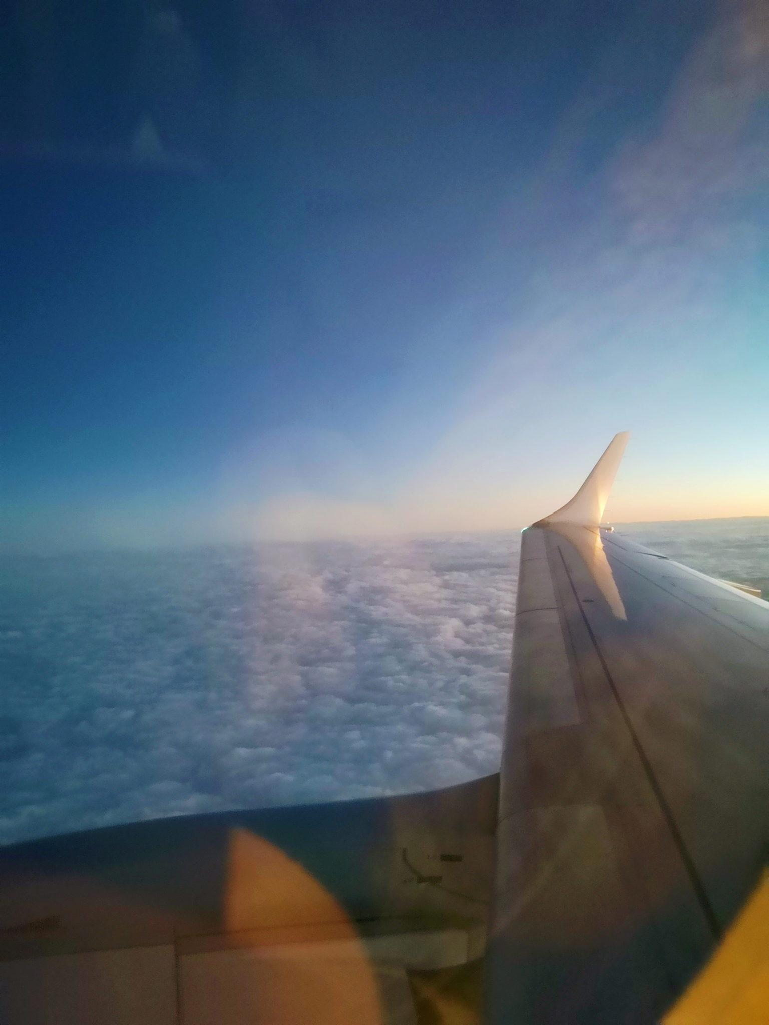 Zdjęcie z okna samolotu: ponad chmurami różowieje wschód słońca