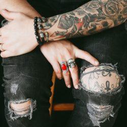 zdjęcie wytatuowanych rąk opartych o wytatuowane kolano w podartych dżinsach