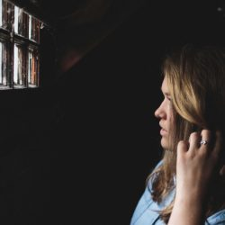 blond dziewczyna stoi w bardzo ciemnym pomieszczeniu, dotykając włosów patrzy w małe okienko