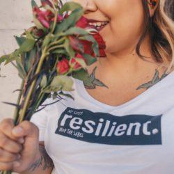 """gruba dziewczyna, widoczna na zdjęciu od nosa do piersi, wącha czerwone kwiaty. Na obojczykach ma wytatuowane jaskółki, a na bluzce napis """"my size? resilient.""""."""