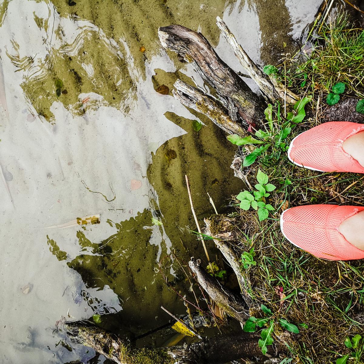 zdjęcie stóp w jaskaroróżowych butach do wody i fragmen brzegu jeziora