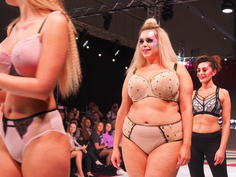 trzy modelki, w centrum kadru modelka plus size Jowita, ubrana w komplet cielistej bielizny z czarnymi i zółtymi akcentami, za nią dojrzała modelka w sportowym stronu - biustonoszu i leginsach
