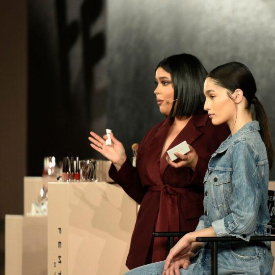 zdjecie przedstawiające Priscille stojącą obok modelki podczas prezentacji makijażu, w tle stojak z produktami Fenty Beauty